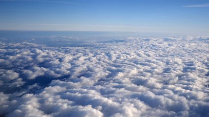 Stunning footage of aerial view above clouds from airplane window with blue sky. view from the airplane window to the blue sky and white clouds. ravelling by air background. Real time footage