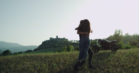 Couple spending time together hugging each other in the middle of amazing landscape they travel together