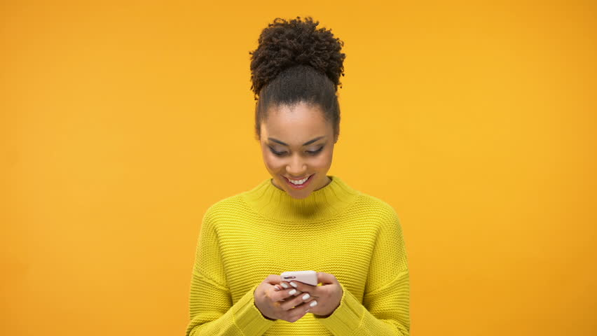 Smiling African-American woman chatting on smartphone and showing ok gesture | Shutterstock HD Video #1024013846