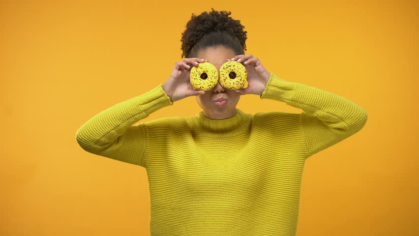 Cheerful Afro-American girl closing eyes with donuts, having fun, background | Shutterstock HD Video #1024014026