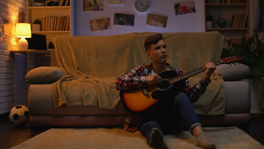 Left-handed teenage student playing guitar at home relaxing after lectures hobby | Shutterstock HD Video #1024016126
