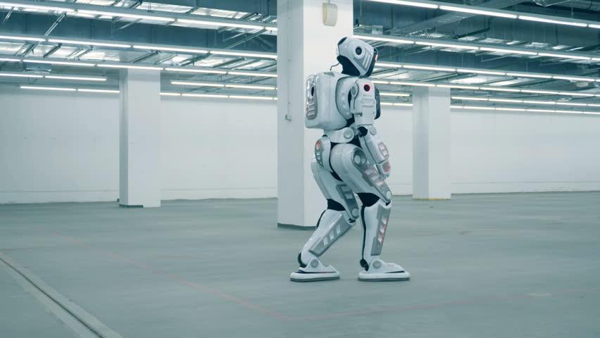 Tall human-like cyborg is walking along an empty warehouse unit | Shutterstock HD Video #1024036946