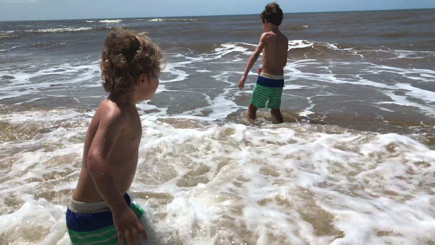 Children playing at the beach with ocean waves | Shutterstock HD Video #1024045436