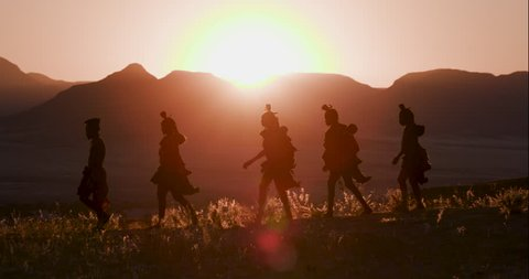 4K view of people from the Himba tribe in traditional dress, walking along a path at sunset with scenic mountains in the background, Namib desert, Namibia