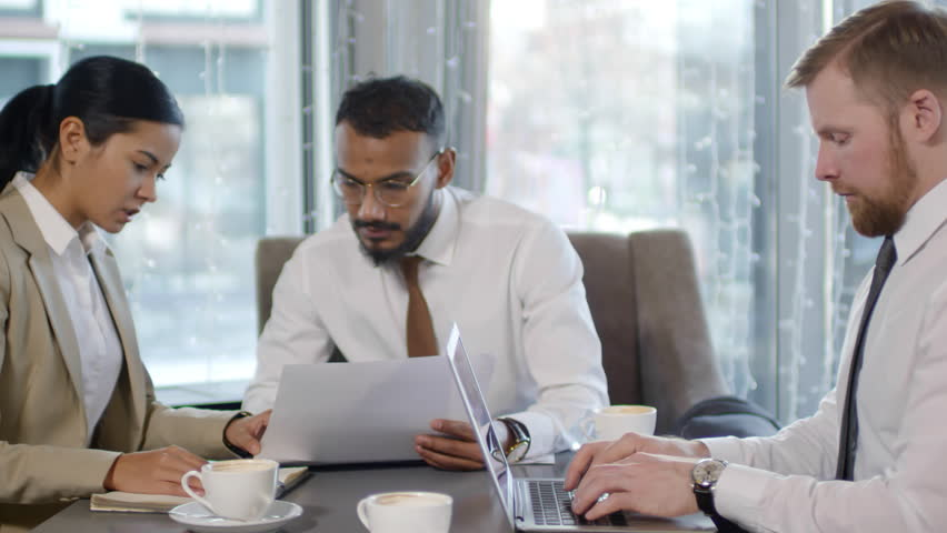 Tracking shot of middle eastern businessman discussing document with female Asian colleague while Caucasian man typing on laptop at cafe table during coffee break | Shutterstock HD Video #1024076216