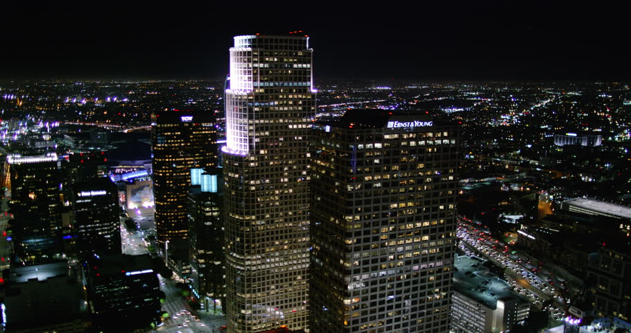 Sexy aerial wide shot of downtown Los Angeles skyscrapers at night showing city lights and building towers from a helicopter point of view with urban streets and traffic. #10240820