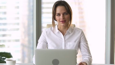 Confident young businesswoman looking talking to camera recording webinar or online training, successful female coach teacher speaking shooting video reportage advertising business services in office