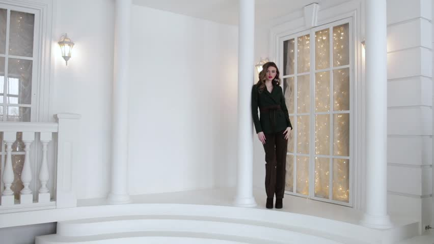 Elegant woman in business suit posing next to tall column and big window, slow motion | Shutterstock HD Video #1024098116