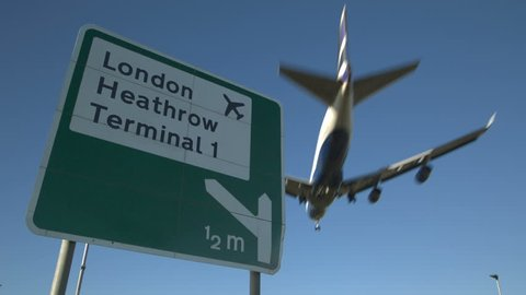Heathrow Airport Sign with aircraft Flyover: Road sign for london heathrow airport with jet airliner flying overhead