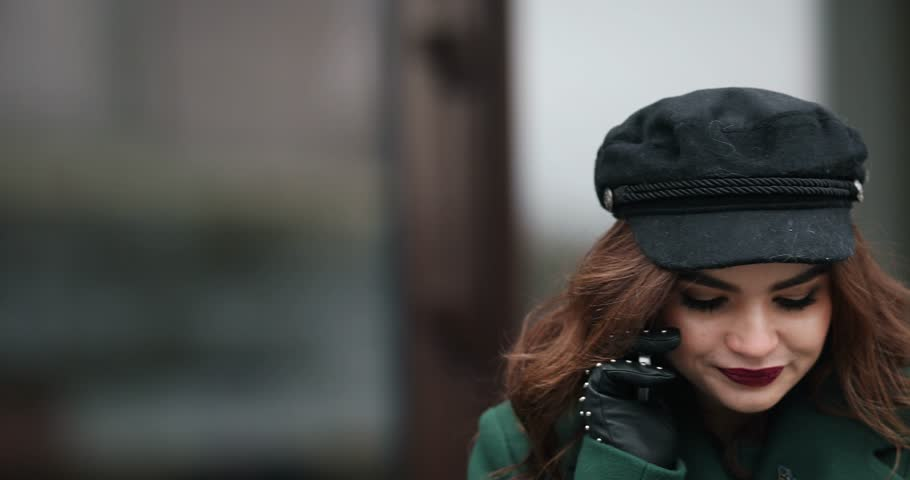 Stylish woman in green coat and beret talking on phone in the street. | Shutterstock HD Video #1024110056