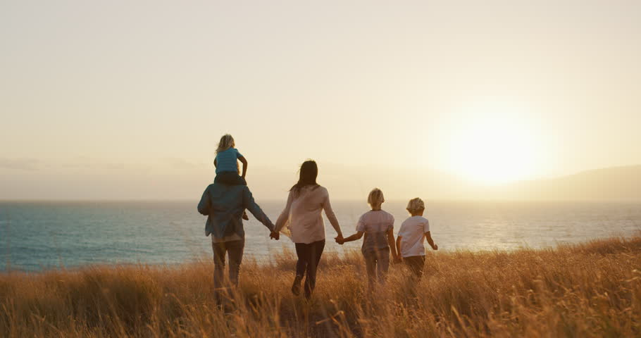 Happy family walking in golden field and looking out to the sunset together by the ocean | Shutterstock HD Video #1024117916