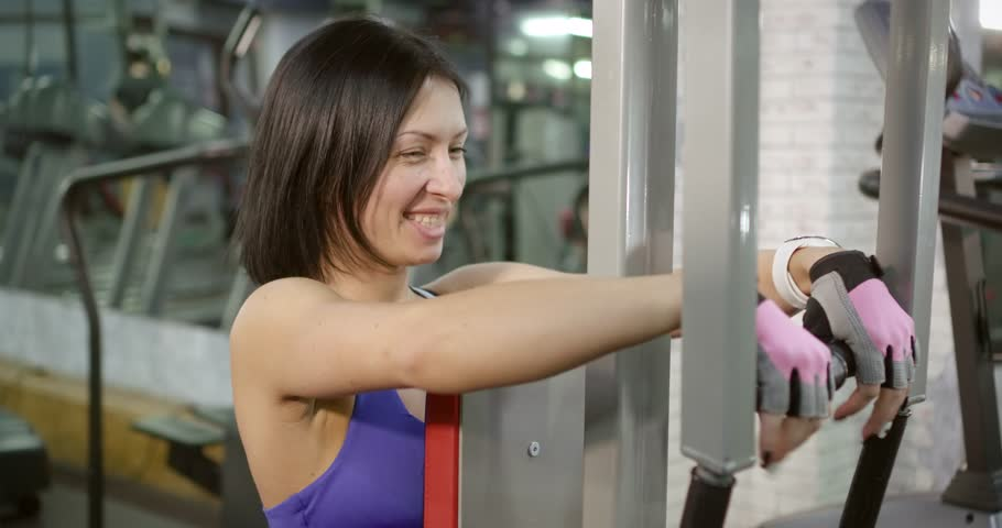 Young woman doing strength exercises hands in the gym with the help of sports equipment. | Shutterstock HD Video #1024140926