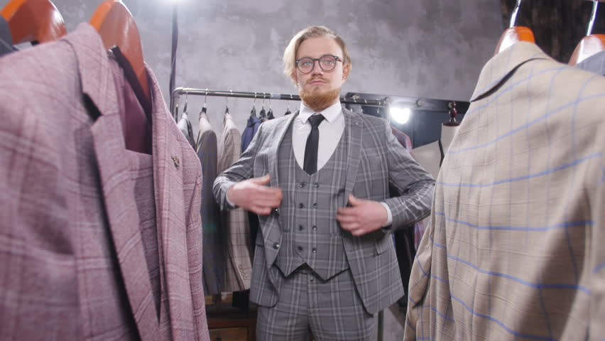 Shopping and fashion concept - Young bearded man choosing and trying jacket on in mall or clothing store | Shutterstock HD Video #1024153316