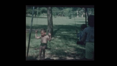 Baltimore, Maryland, USA - 1963: Girls stops by to push boy on swing