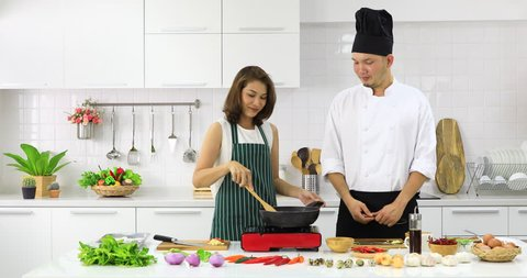 Beautiful Asian housewife learning how to cook with professional chef in new clean and modern kitchen.