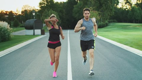 Sport couple run together in park. Young people jogging together at fitness training outdoor. Man and woman at sport training together