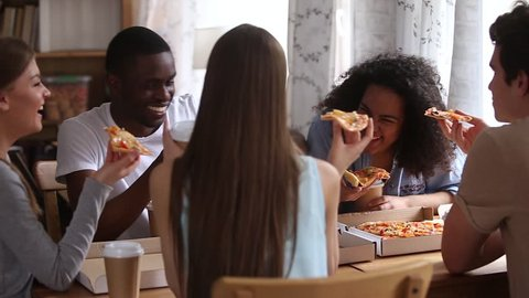 Happy diverse friends eating pizza drinking coffee share dinner meal at home restaurant, multiracial young people students laughing talking having fun conversation at cafe pizzeria restaurant meeting