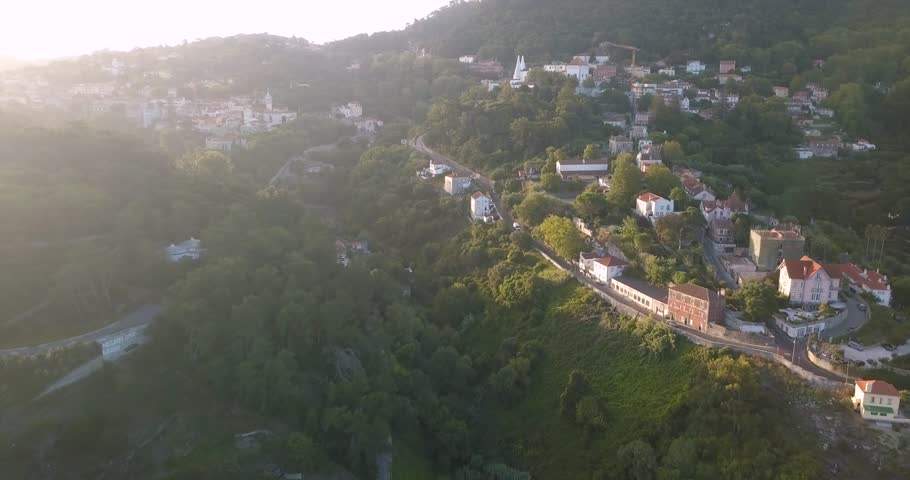 Stunning aerial view of the historical village, Sintra in Portugal. Beautiful sunrise, drone flies backwards. Green trees, mountains and stunning architecture.