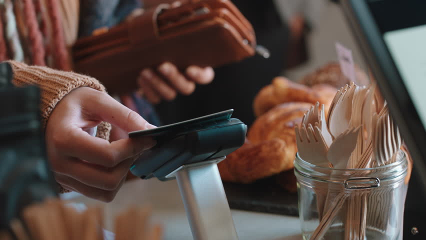 Close up customer paying using credit card contactless payment spending money in cafe with digital transaction service | Shutterstock HD Video #1024313396