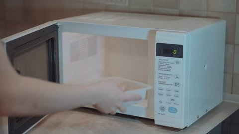 Heated food in the microwave. Female hand puts pies in the microwave in the lunch box. Cooking in the microwave. 4k video.