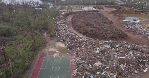 Drone shot flying above a mound of trash and debris from destroyed property and trees in the aftermath of Hurricane Michael
