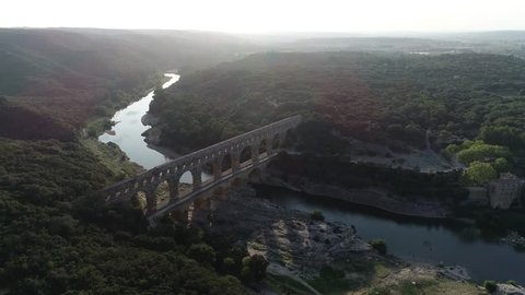 Aerial view of Pont du Gard is ancient Roman aqueduct that crosses the Gardon River near the towns of Remoulins Avignon and Nimes in southern France and is on UNESCO's list of World Heritage Sites 4k