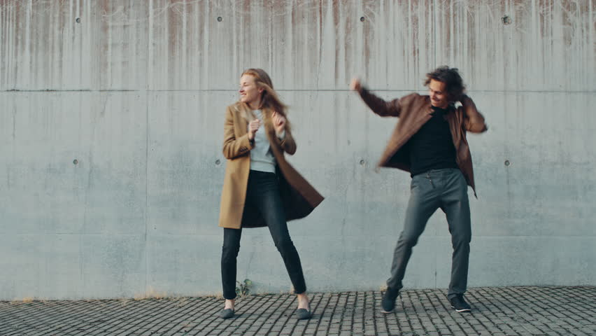 Cheerful Girl and Happy Young Man with Long Hair are Actively Dancing on a Street next to an Urban Concrete Wall. They Wear Brown Leather Jacket and Coat. Sunny Day. | Shutterstock HD Video #1024342526