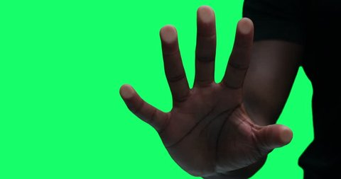 Hand pressing against transparent glass in front of the camera with green screen. For compositing, visual effects, video production. 4k shot.