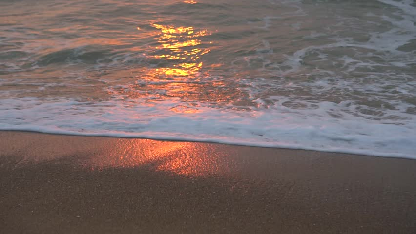 Amazing sunset over the tropical beach. Waves on the beach in the tropics at dawn, Morning at sea, sunrise on the sea beach, orange sunlight.