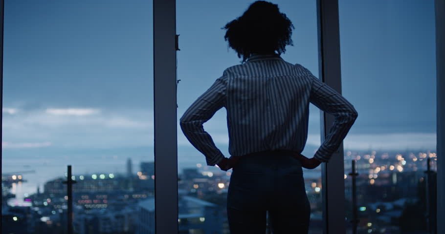 Young woman looking out window enjoying view of city at night contemplating successful lifestyle planning ahead on calm urban evening | Shutterstock HD Video #1024427906