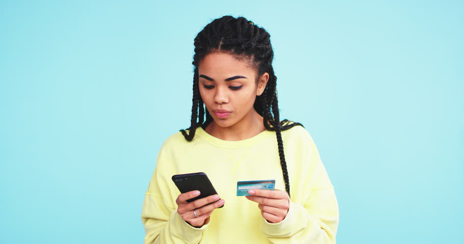 African pretty lady using a credit card and make a online order with her smartphone on a blue background wall.