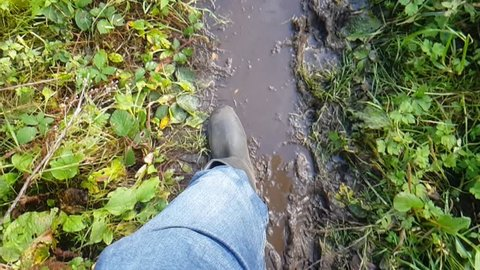 Slow motion walking with Wellington boots though mud and leaves