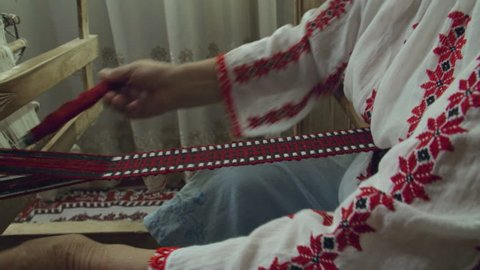 A dolly out shot of weaver who is weaving a traditional belt on a obsolete wooden weaving machine.