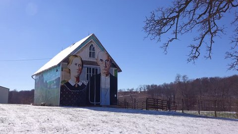 AMERICAN MIDWEST - CIRCA 2018 - A rural barn has a rendition of Grant Wood's American Gothic painting on the side.
