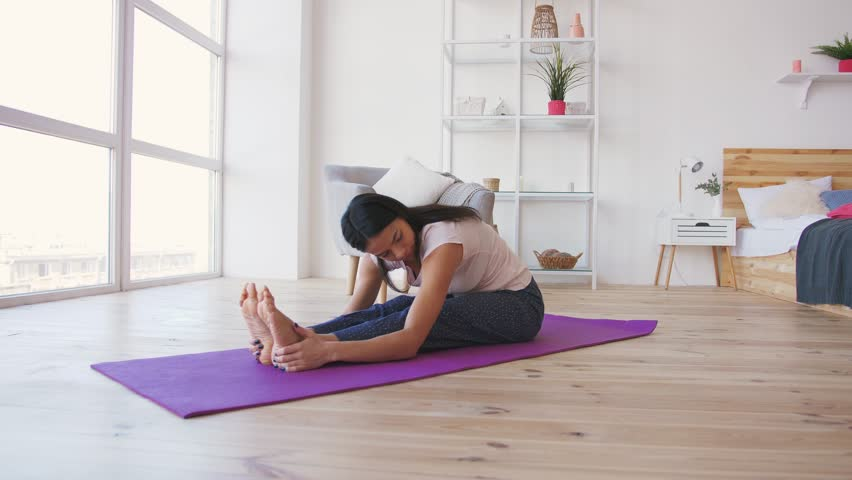 Young adult female doing yoga at home | Shutterstock HD Video #1024562636