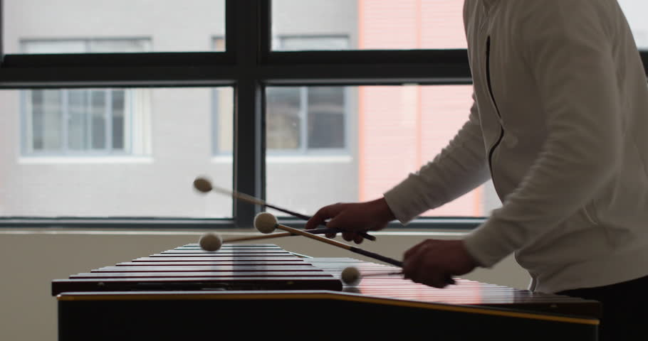 side face of handsome Caucasian man percussionist playing marimba percussion instrument with window in background. creative artist playing beautiful melody on wooden instrument with drumsticks