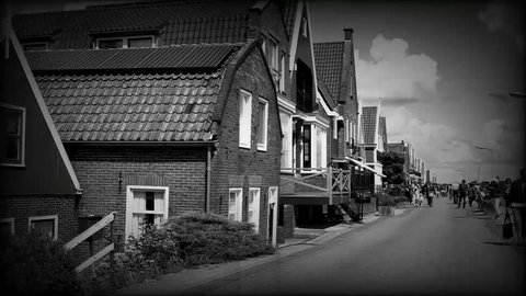 Volendam, Netherlands -August 18, 2018: Tourists walking near typical small Dutch houses with beautiful facades in Volendam, 4K. Effect old movie