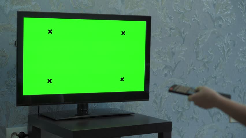A Female hand switches channels on a TV with a green screen. TV stands on a small black table. Monitor in a room with blue wallpaper. | Shutterstock HD Video #1024603796