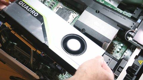 Paris, France - Feb 20, 2019: Man installing the latest Nvidia Quadro RTX 5000 workstation professional video card GPU in Dell Precision T7910 workstation