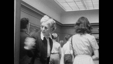 1940s: People walking through the Museum of Modern Art, looking at paintings on display.