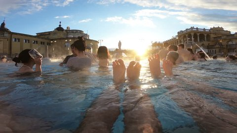 HUNGARY, BUDAPEST - FEB 21, 2018: Young couple enjoys swimming in outdoor warm thermal pool in winter. Szechenyi medicinal bath is largest therapeutic swimming complex with thermal springs in Europe