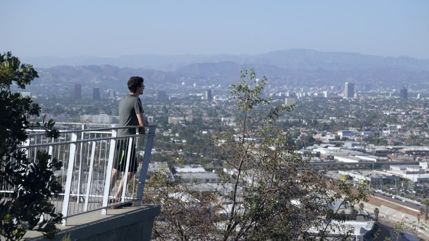 Young man enjoys the views of his city after a long hike to a great overlook. | Shutterstock HD Video #1024773776