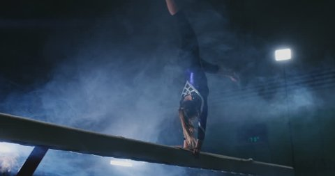 Legs Professional girl gymnasts jump in slow motion in the smoke on the balance beam. Women's Artistic Gymnastics