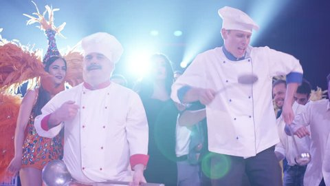 Cook and waiter dancers having fun dancing at a colorful party . Funny cook chef and waiters in white uniform, with a hat and ladle , smiling and partying during party . Cinema Camera in slow motion .