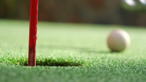 Golf ball dropping into a hole and pulling it out in 4k slow motion 60fps