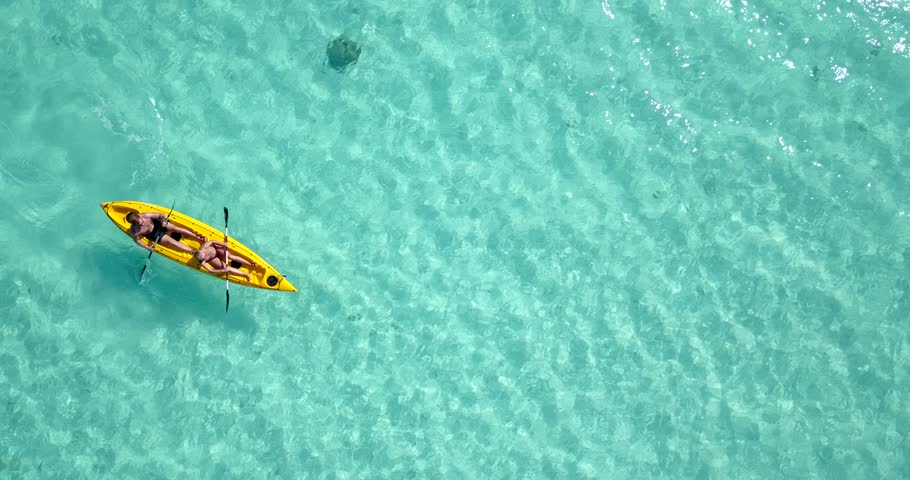 Looking down from above as two men paddle their yellow sea kayak through gorgeous clear blue water in Seychelles. Aerial, lookdown, 4k.