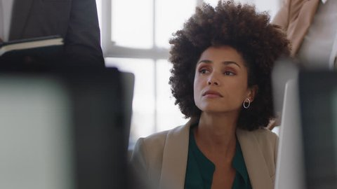 beautiful african american business woman taking notes in office meeting brainstorming ideas planning strategy