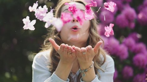 Woman Enjoying Spring Blossom. SLOW MOTION. Happy Smiling Girl blowing on rhododendron flower petals, making them fly to camera. Sunny Spring Outdoors Activity, Lens Flare.