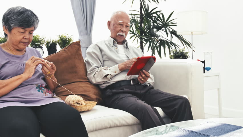 Asian senior man using tablet computer and Senior Woman Knitting with Wool, Grandmothers Hands Knit Wool Yarn. Craft is Hobby of Old Women and having knee pain.   Shutterstock HD Video #1025035286