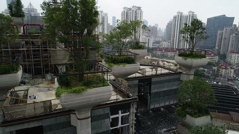 SHANGHAI, CHINA - SEPTEMBER 2018: Close drone flight past trees on columns, part of a sustainable housing project under construction in Shanghai, China